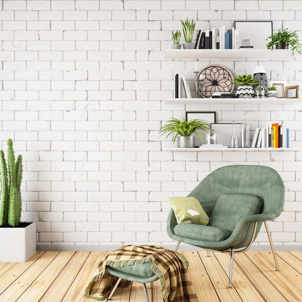 Scandinavian themed reading area with wooden flooring, minimalist designed bookshelf and a green chair