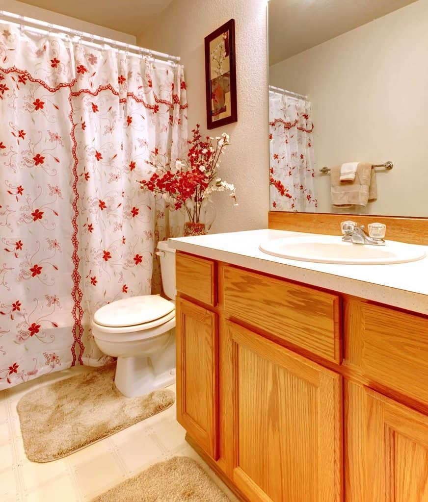 Simple bathroom with flowery shower curtain and wood cabinet
