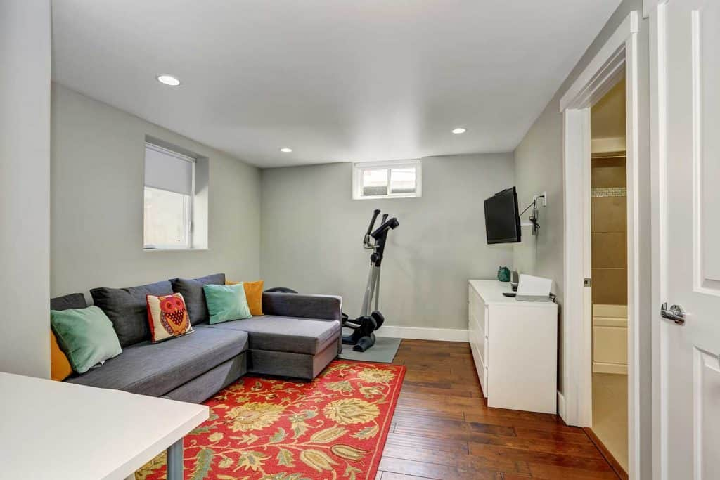 Sitting room interior with sport equipment in the basement and corner sofa
