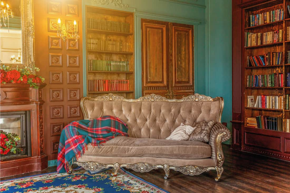 Sitting room with bookshelf, books, arm chair, sofa and fireplace in new Victorian style living room