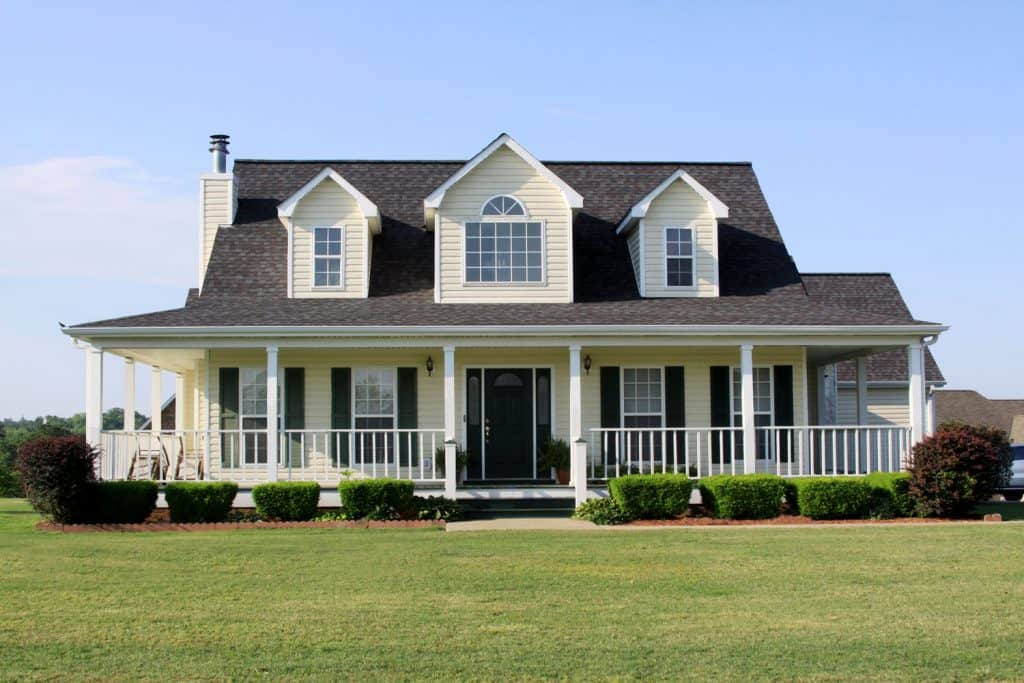 Small modern American country house with brown shingle roofing and cream painted wooden sidings