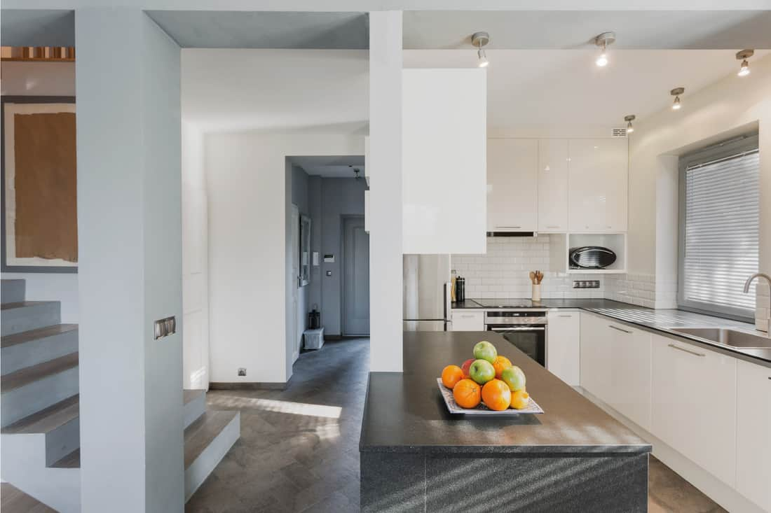 Small white luxurious kitchen with marble black counter and bright spotlight lighting