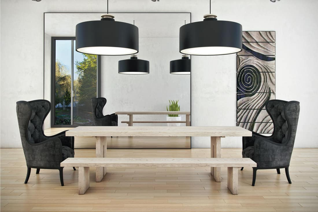 Space of meeting dining room with big center minimally framed mirror and two dark contrasted chairs.
