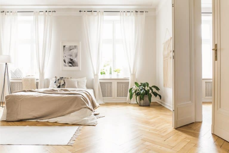 Spacious and bright bedroom interior with beige decorations, hardwood floor and a tab type curtain, How To Hang Tab Curtains