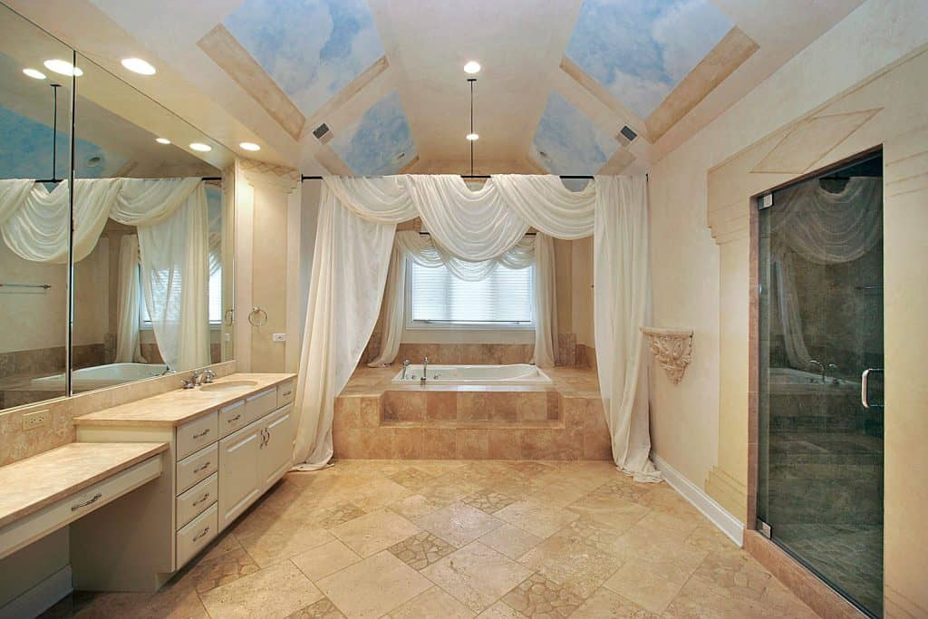 Spacious bathroom with gorgeous brown tiles, small bathtub, and a huge vanity area with cream colored cabinets