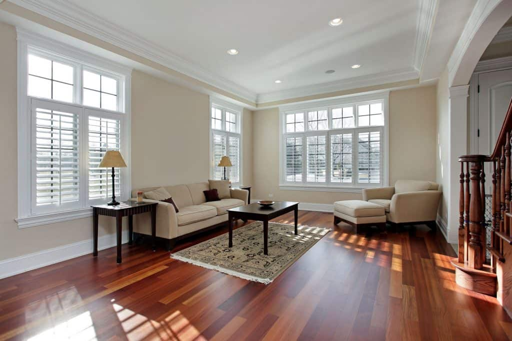 Spacious modern living room with white hardwood flooring, white sofas, black wooden end table, and cream painted walls