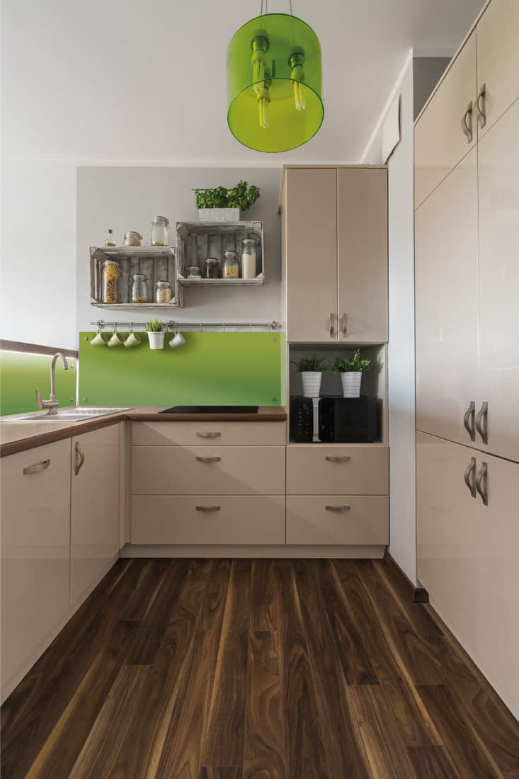 Stylish and bright kitchen interior design in beige and green with elegant wooden floor, vibrant accent color
