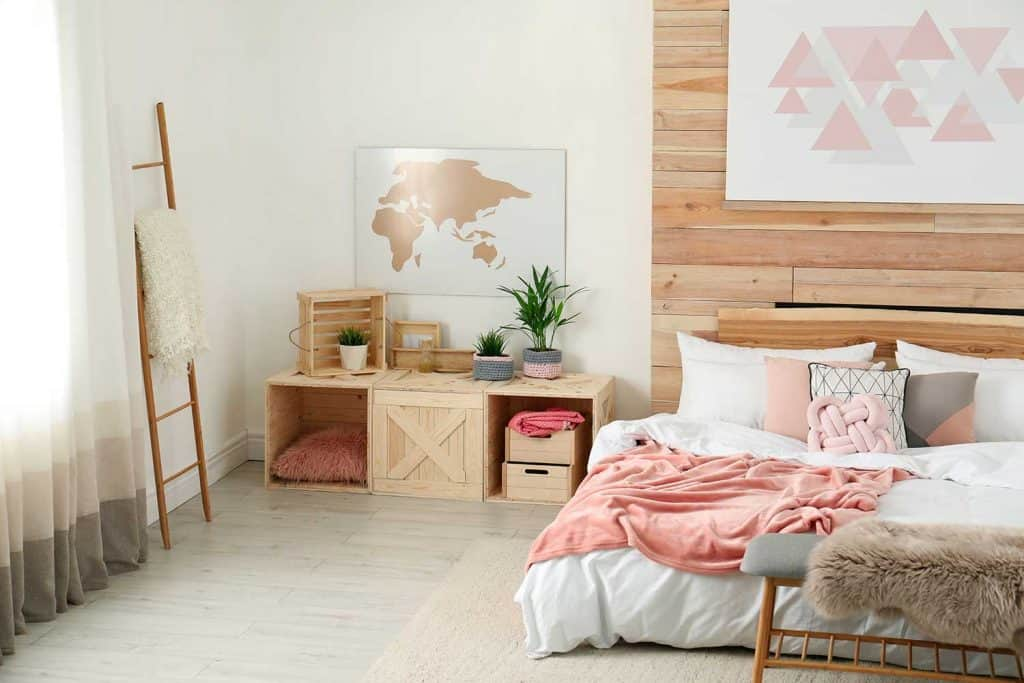 Stylish room interior with comfortable bed near wooden wall