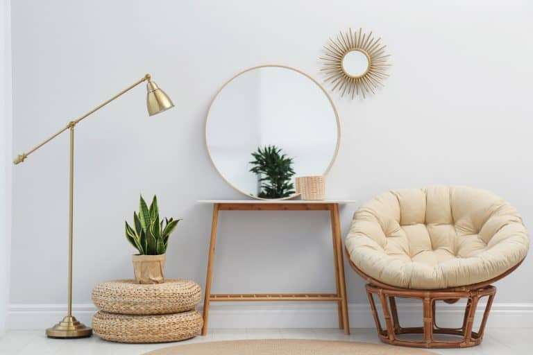 Stylish round mirror near white wall in room with papasan chair, 13 Types Of Living Room Chairs