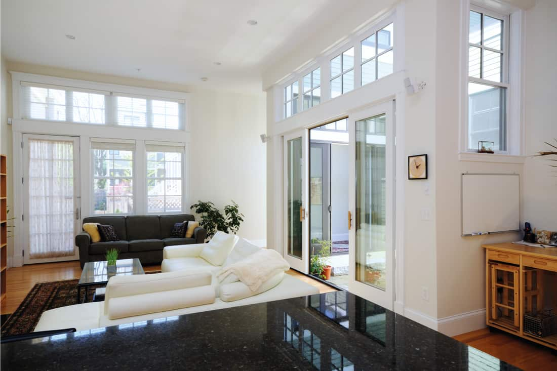 Sunny home interior of open plan apartment showing living room with screen doors and sliding doors