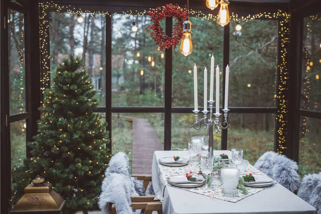 Table at cottage green house decorated for Christmas dinner., festive window treatment