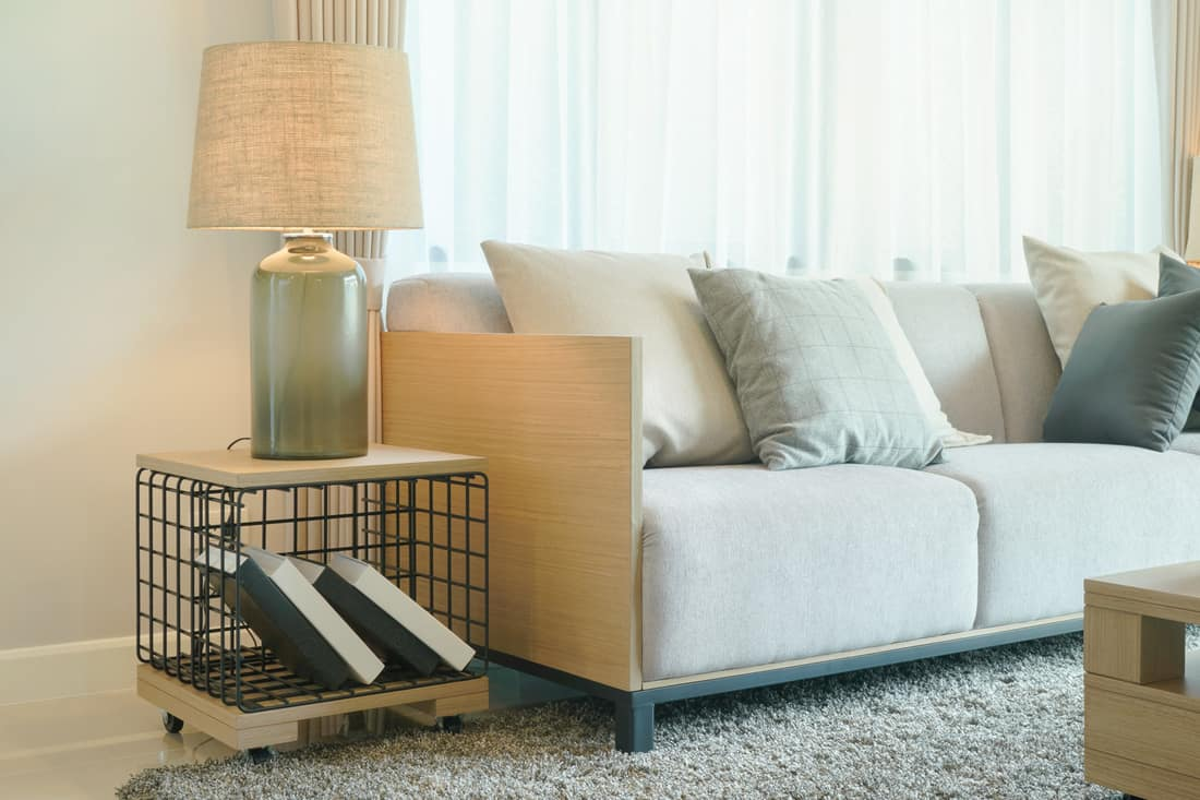 Table lamp and end table next to comfy sofa in modern style living room