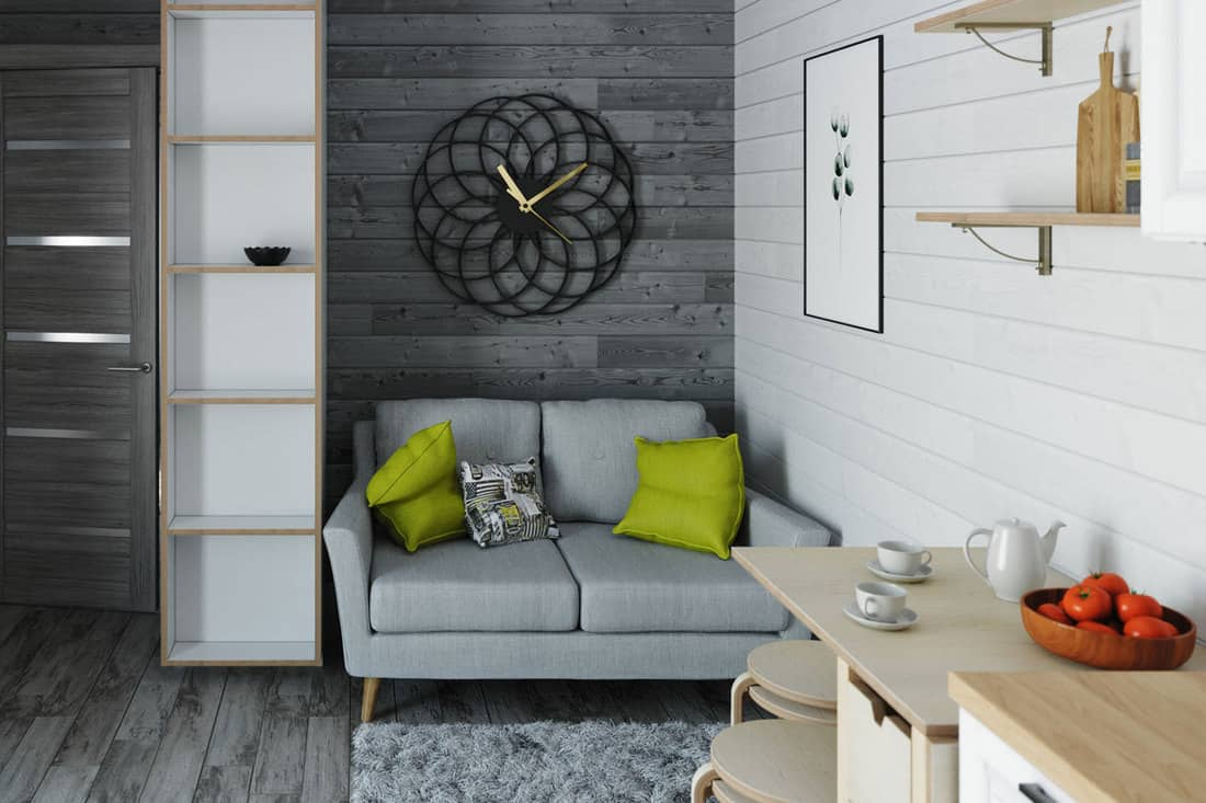 The interior of a small living room with loveseat sofa