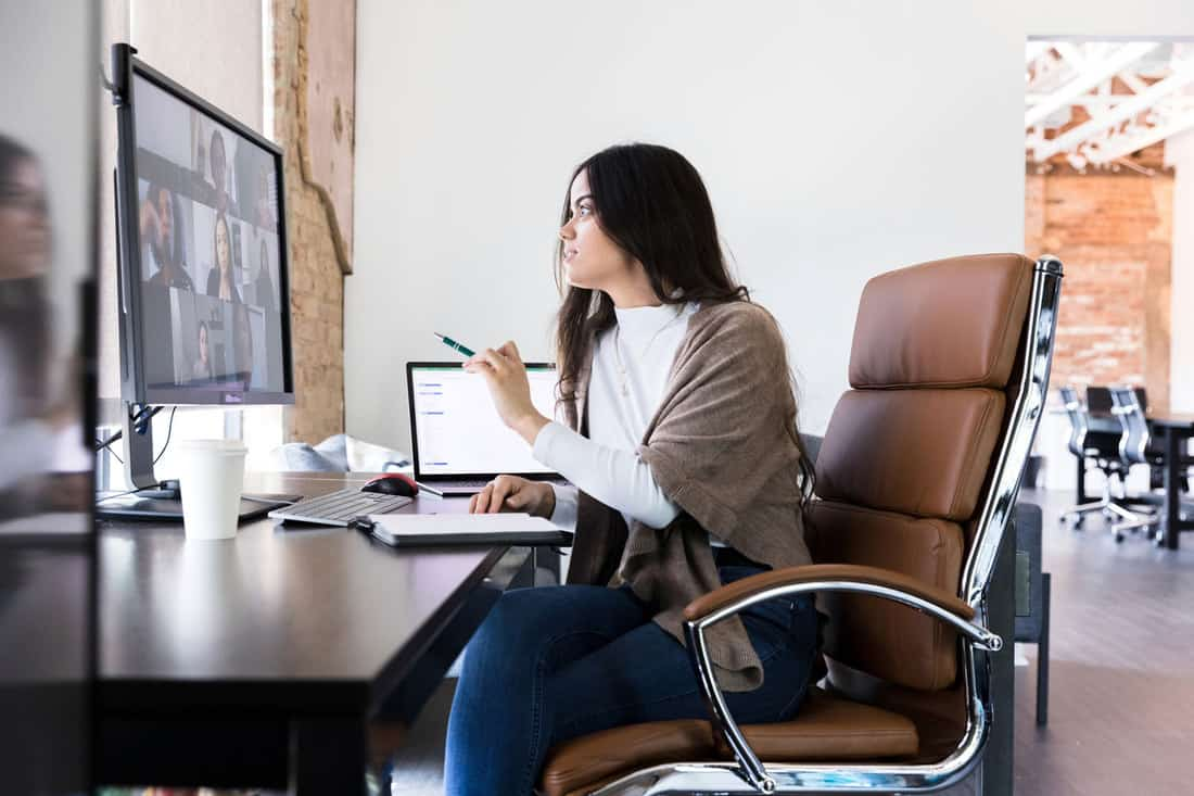 The young business owner checks in with her employees via video conferencing sitting on a brown leather office chair
