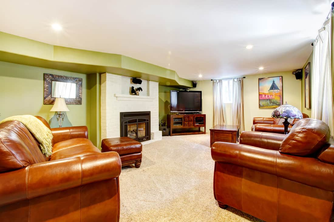 Tv room with green walls, leather sofas