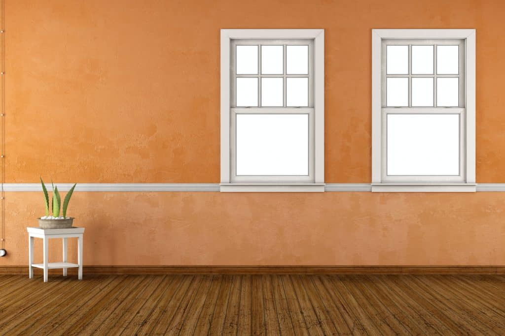 Two double hung windows inside an orange colored living room