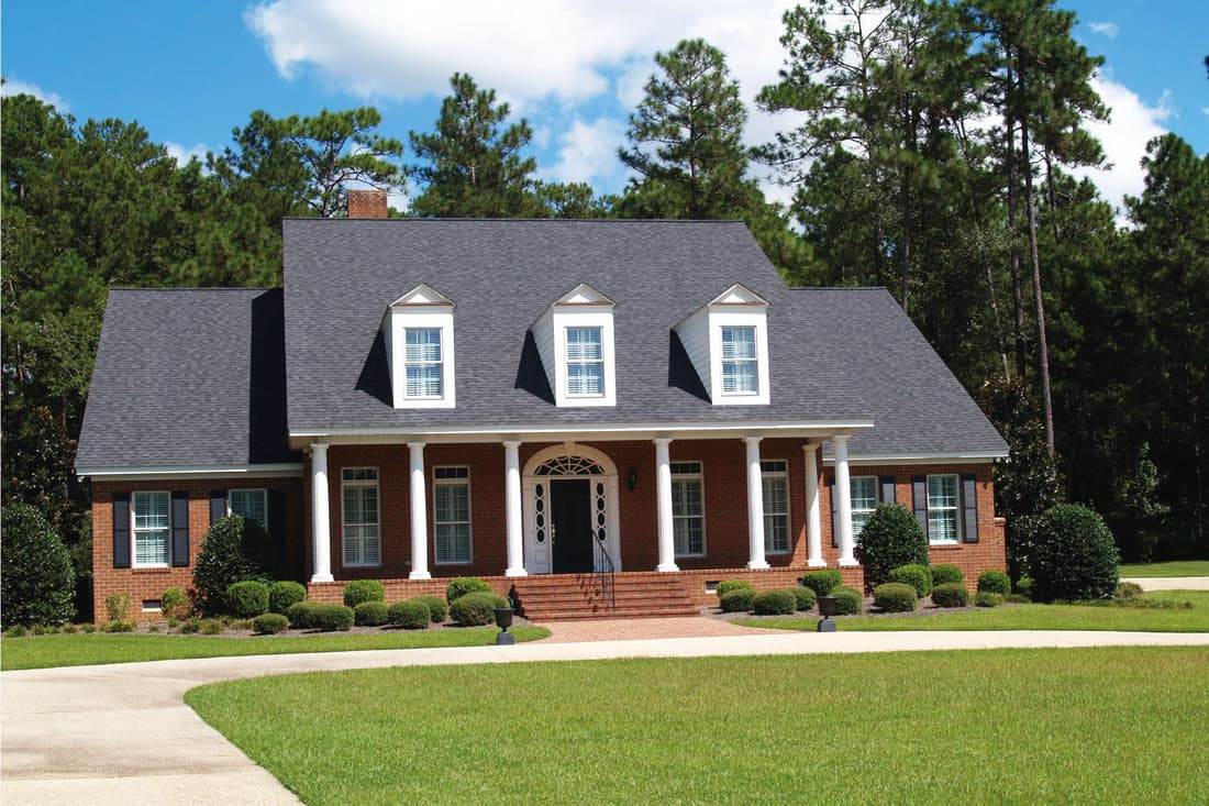 Two-story brick residential home with large front porch, side entrance garage and gray roof