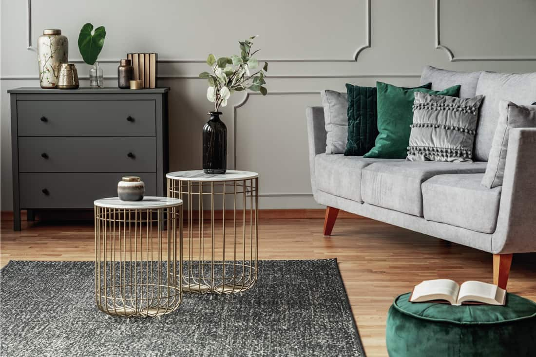 Two stylish small coffee tables with marble tops in front of elegant grey couch with emerald pillows and ottoman seat