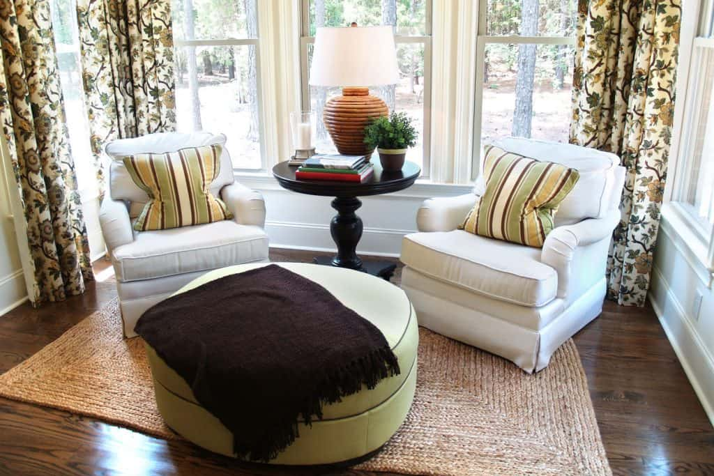 Two white gorgeous loveseats with striped throw pillows on it and a handcrafted nightstand on the center