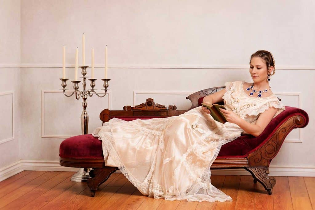 Victorian woman reading book on fainting couch