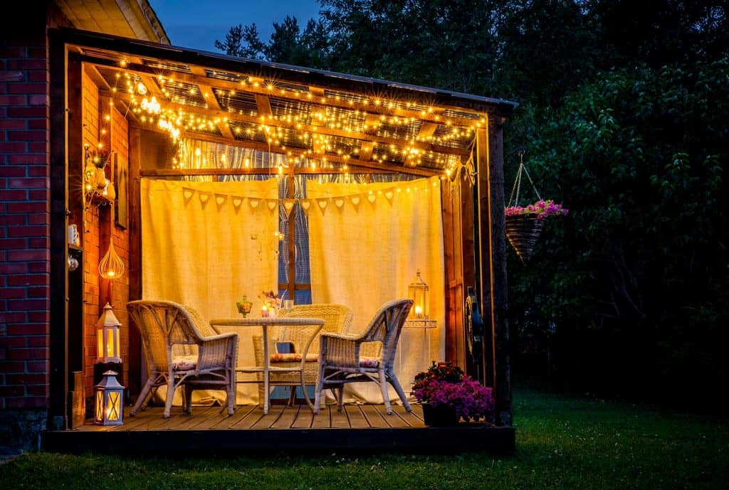 View over cozy outdoor terrace with table and chairs, very romantic lighting, white lanterns, candles burning, led string party lights and bulbs with star effect in the evening