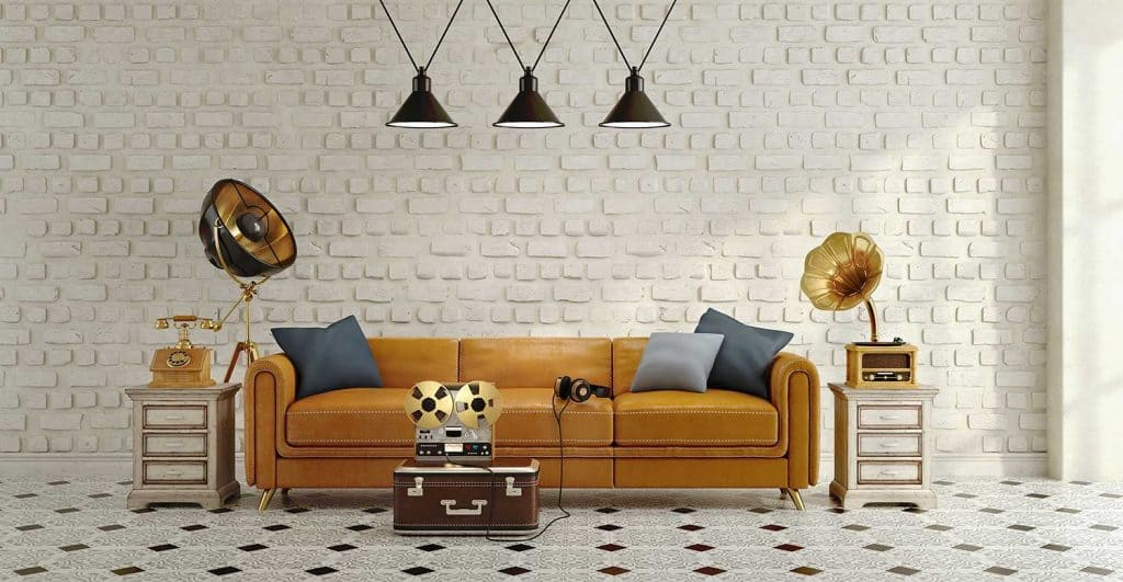 Vintage style interior with beige leather sofa with pillows, side table, black ceiling lamp, white brick background and tiled floor