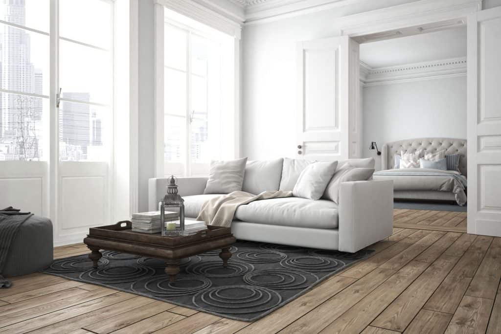 Vintage styled living room with wooden flooring, white sofas with a wooden coffee table, and white painted walls