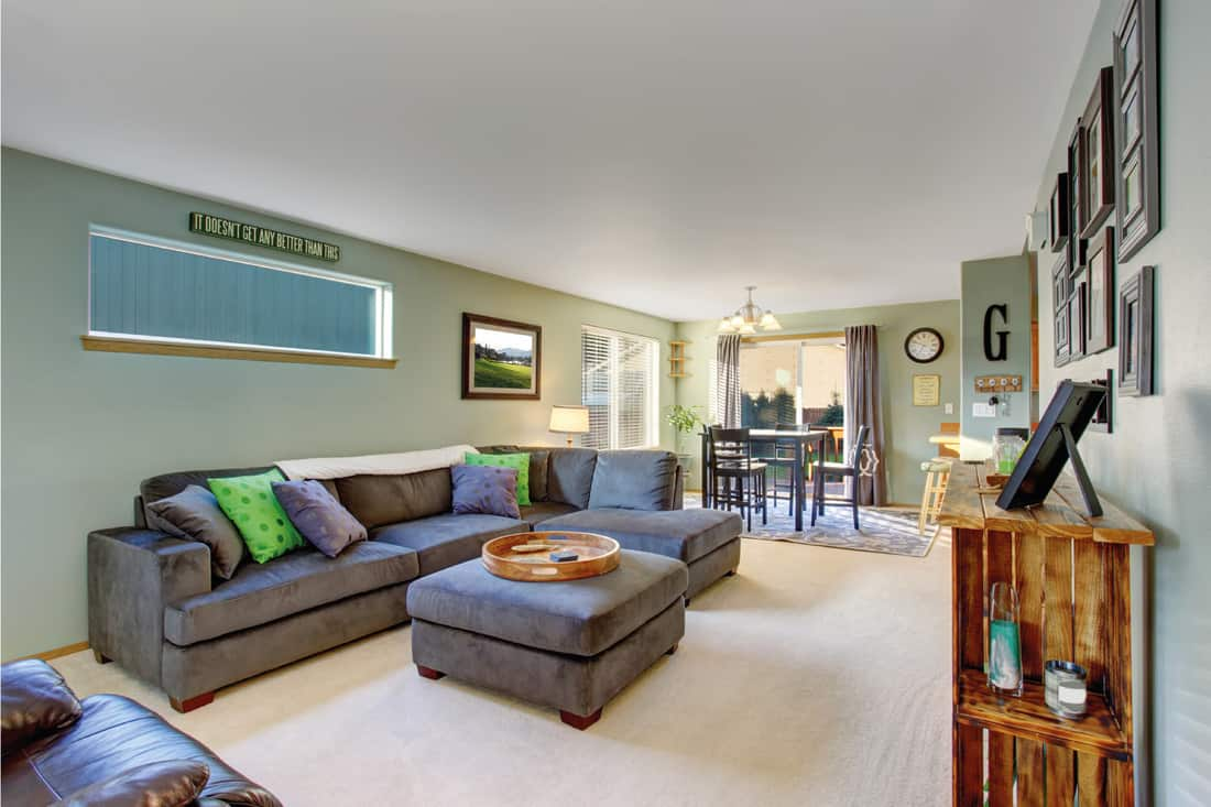 Walls in sage green, gray sectional sofa, picture frames on the wall