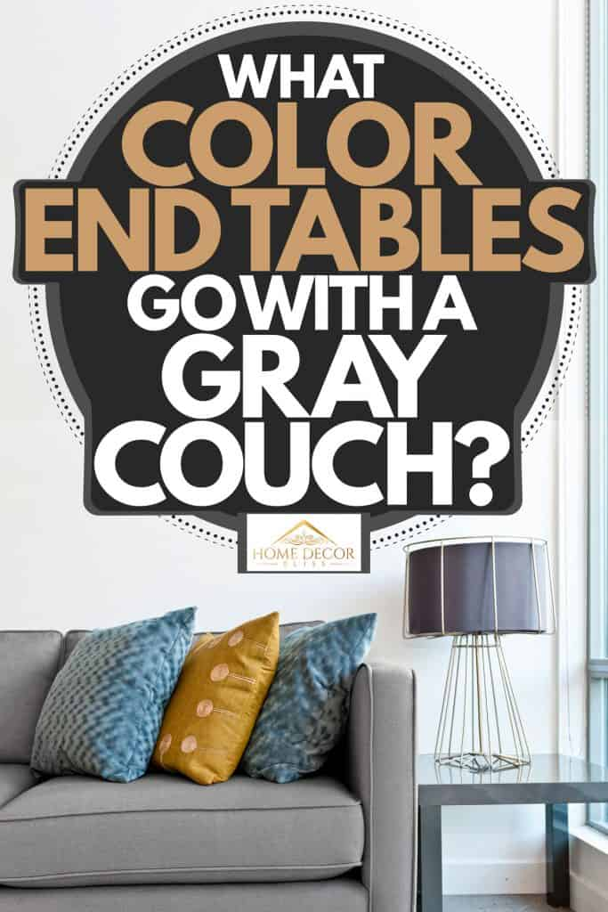 A gray sectional sofa with throw pillows placed next to a metal end table with a lamp on top, What Color End Tables Go With A Gray Couch?