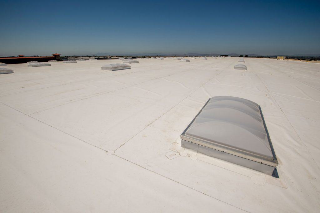 White PVC membrane laid on the roof of a large warehouse