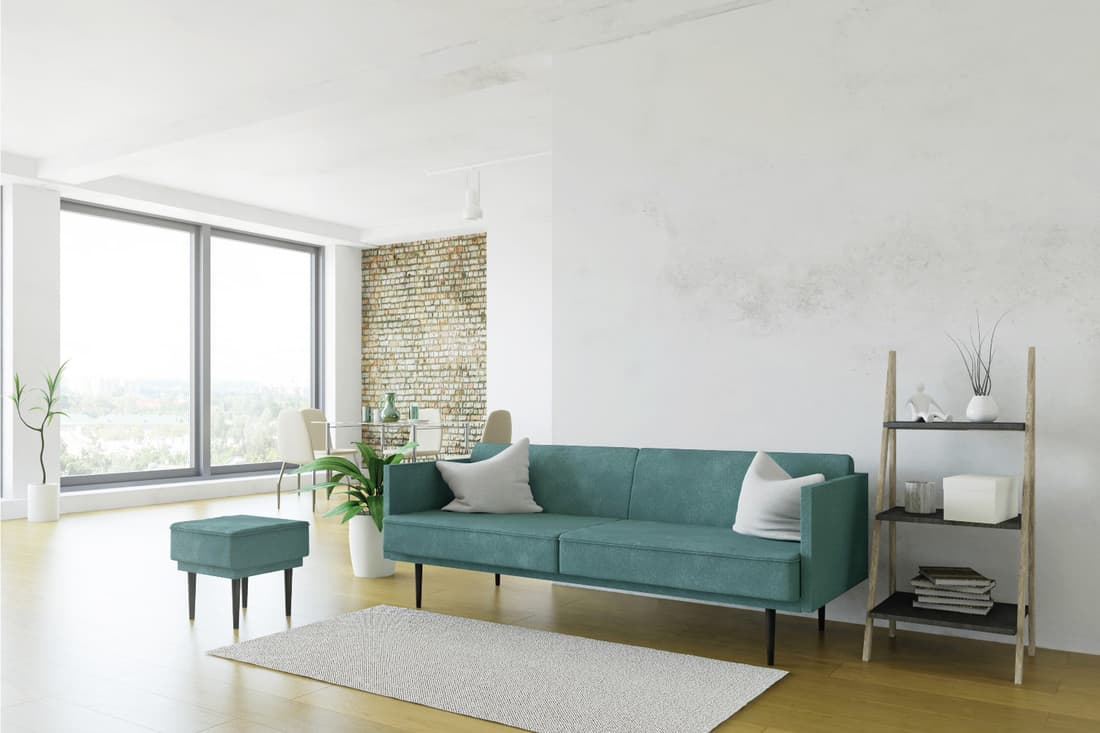White room minimalistic design, turquoise sofa and ladder shelf, table with chairs near the window, textured brick accent wallpaper