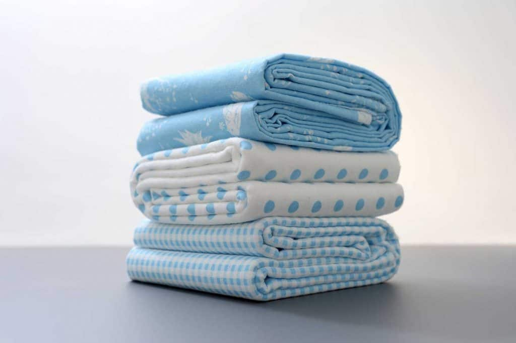White and blue baby bed sheets