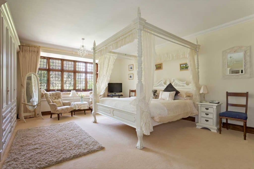 White four-poster bed in large neutral-colored bedroom