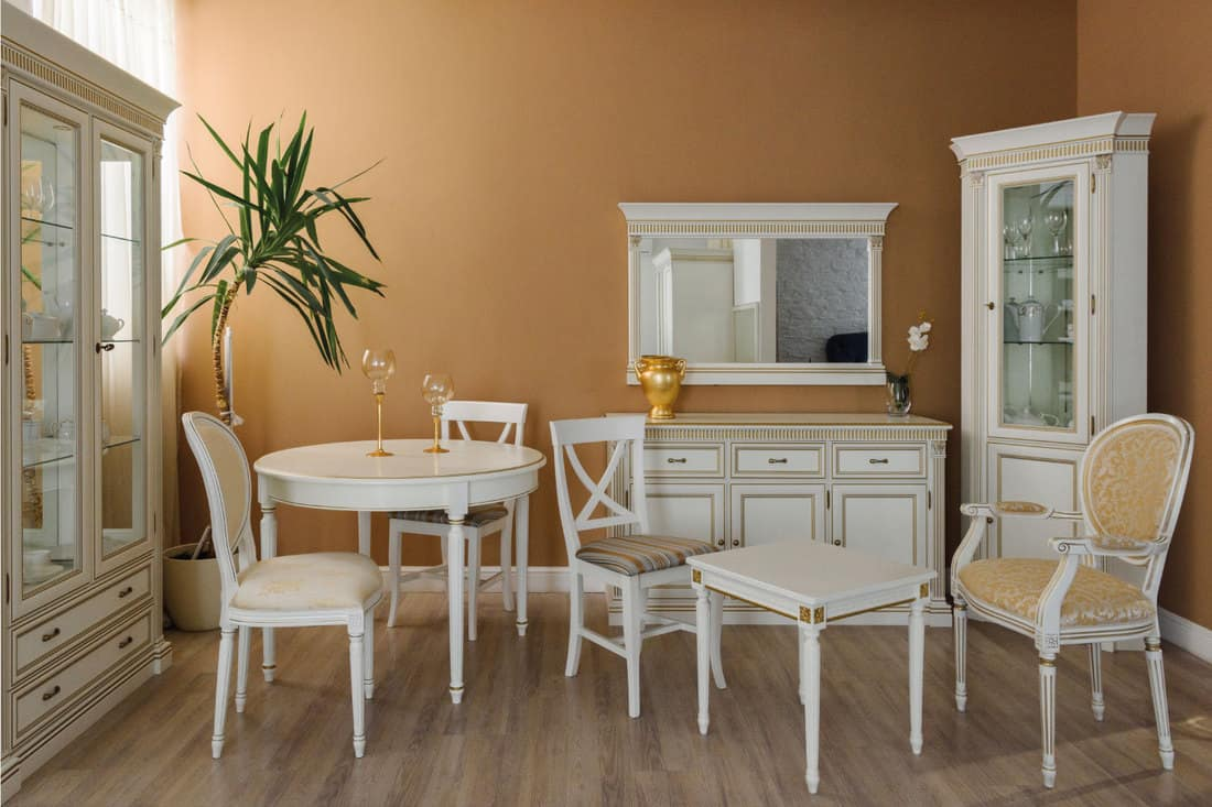 White furniture in elegant dining room, mirror on the wall woth ornate frame matching the furniture