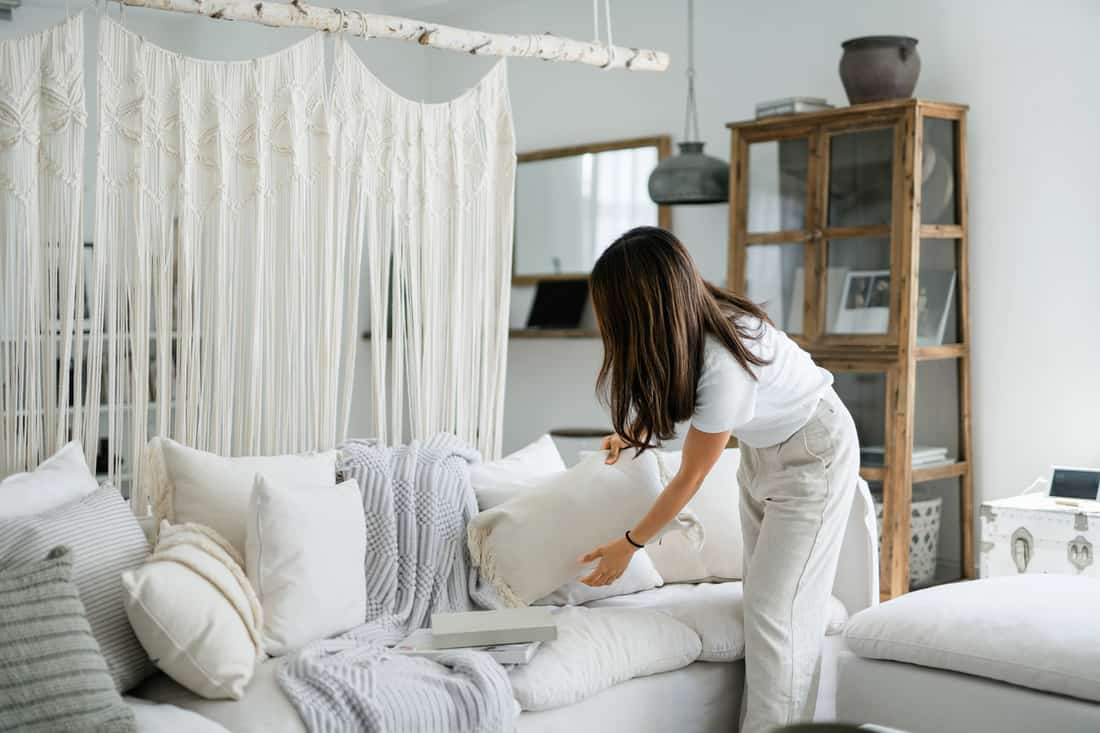 Young Asian woman organising and tidying up the cushions on the sofa in the living room