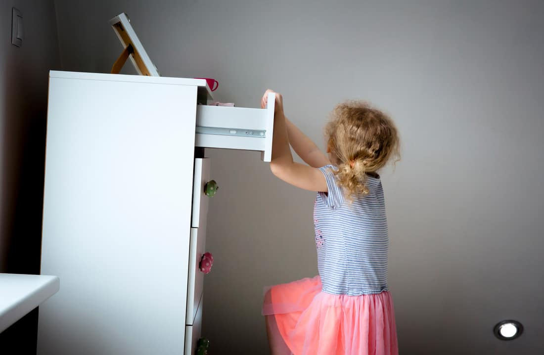 Young girl child climbing on modern high dresser furniture, danger of dresser dipping over concept.