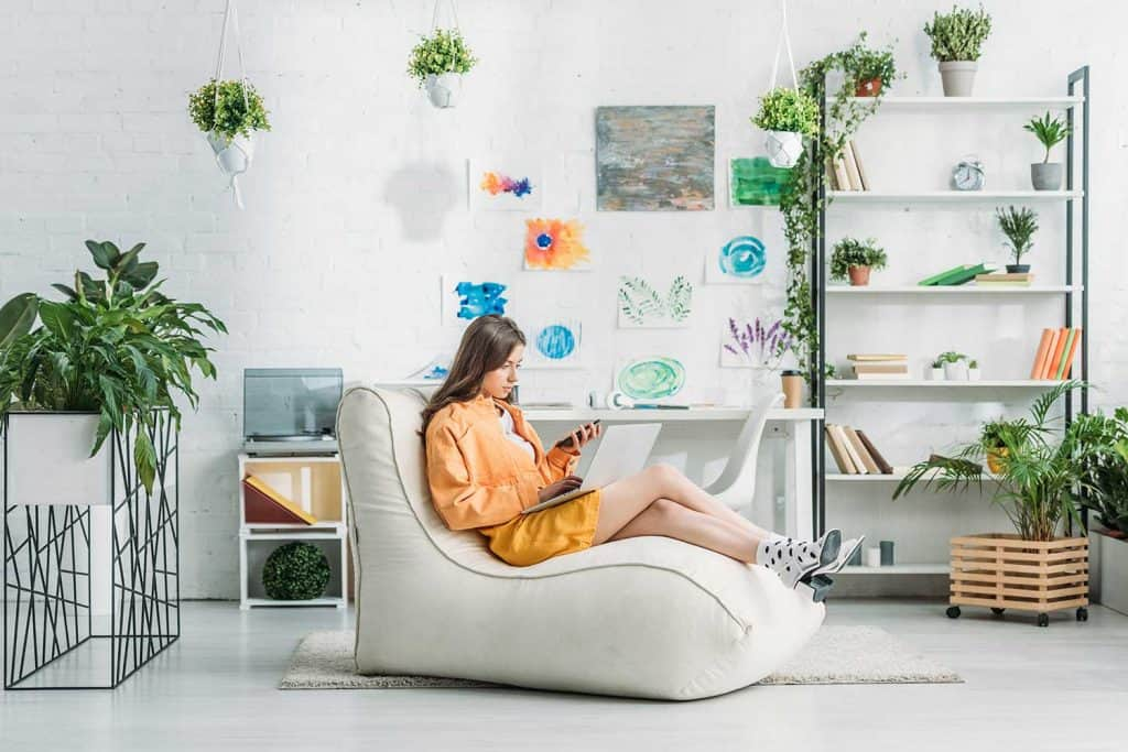 Young woman using laptop and smartphone while sitting on soft chaise lounge in spacious room