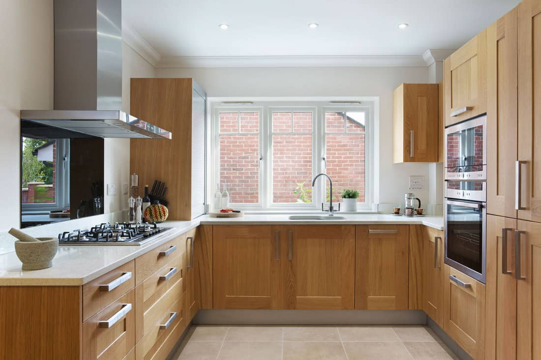 a beautiful kitchen in a modern apartment with oak fitted cupboards and drawers and cream coloured granite work top, How To Restore Oak Cabinets [5 Steps]