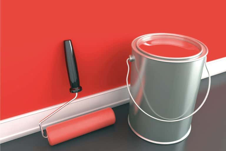 A can of red paint and a roller against a painted wood wall, How To Paint Wood Siding With A Roller [6 Steps]