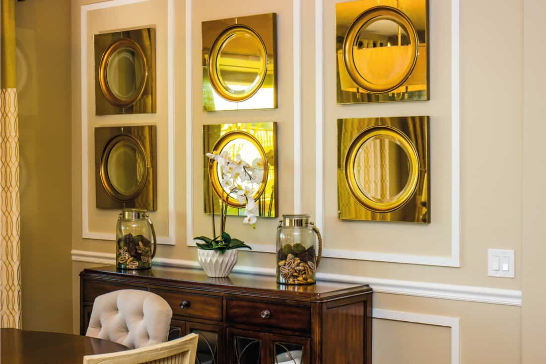 a group of small brass mirrors on a wall above a buffet