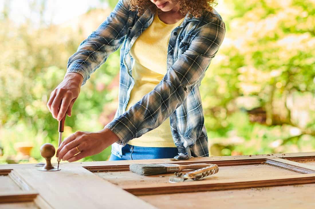 a woman sands a vintage wooden door