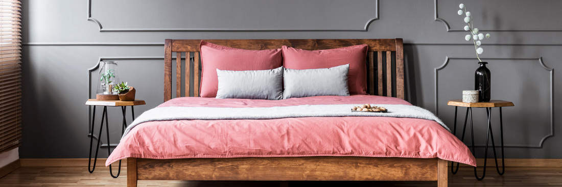 a wooden king-size bed with pink bedding standing in dark grey bedroom interior with wainscoting on wal