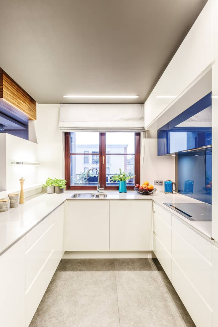 All white kitchen interior with a window in the center, elegant countertops and blue modern glass elements