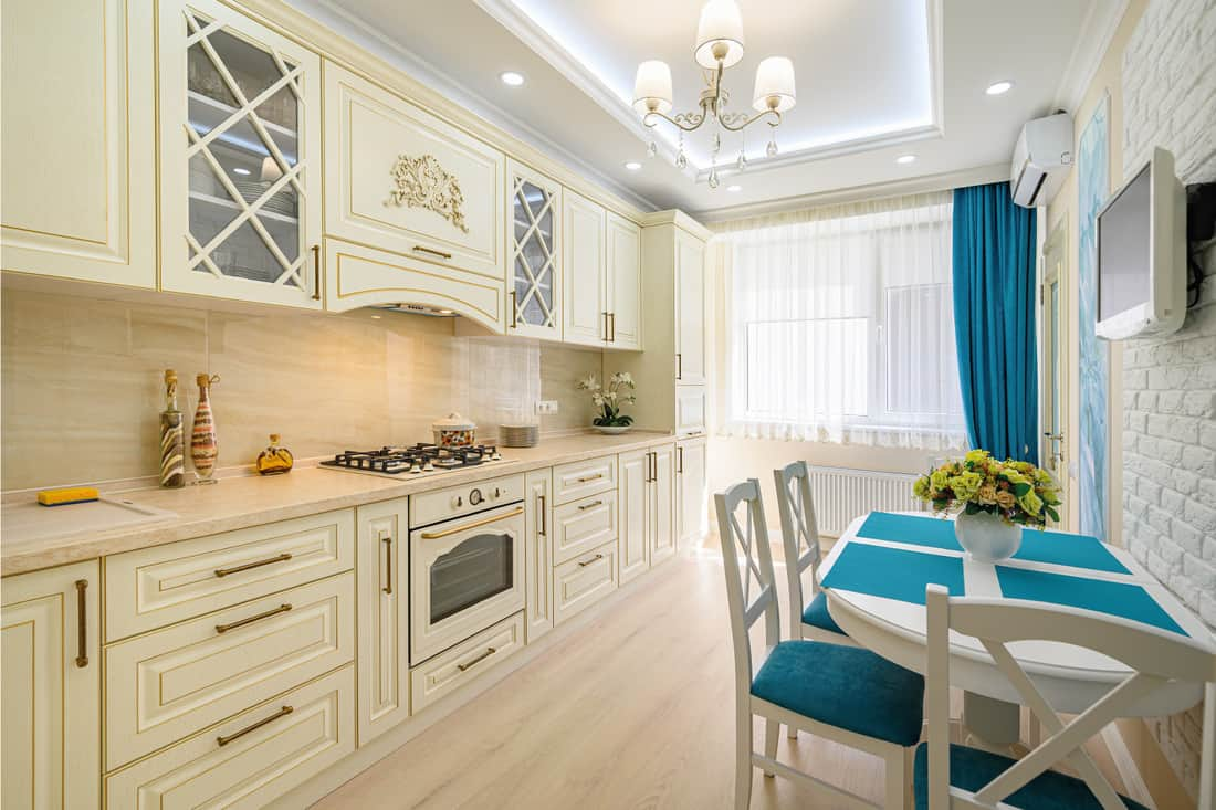 Beige, white and cyan classic kitchen, layered color-coordinated curtains, all furniture with open doors and drawers