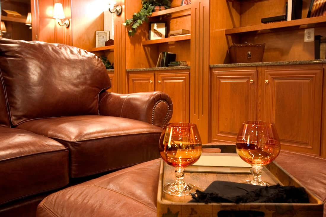 Brandy glasses on leather ottoman in a living room