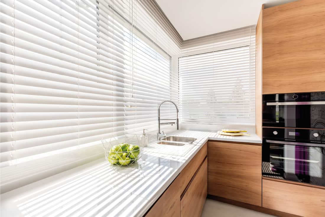Bright kitchen interior with wide horizontal venetian window blinds, wooden cabinets with white countertop and household appliances
