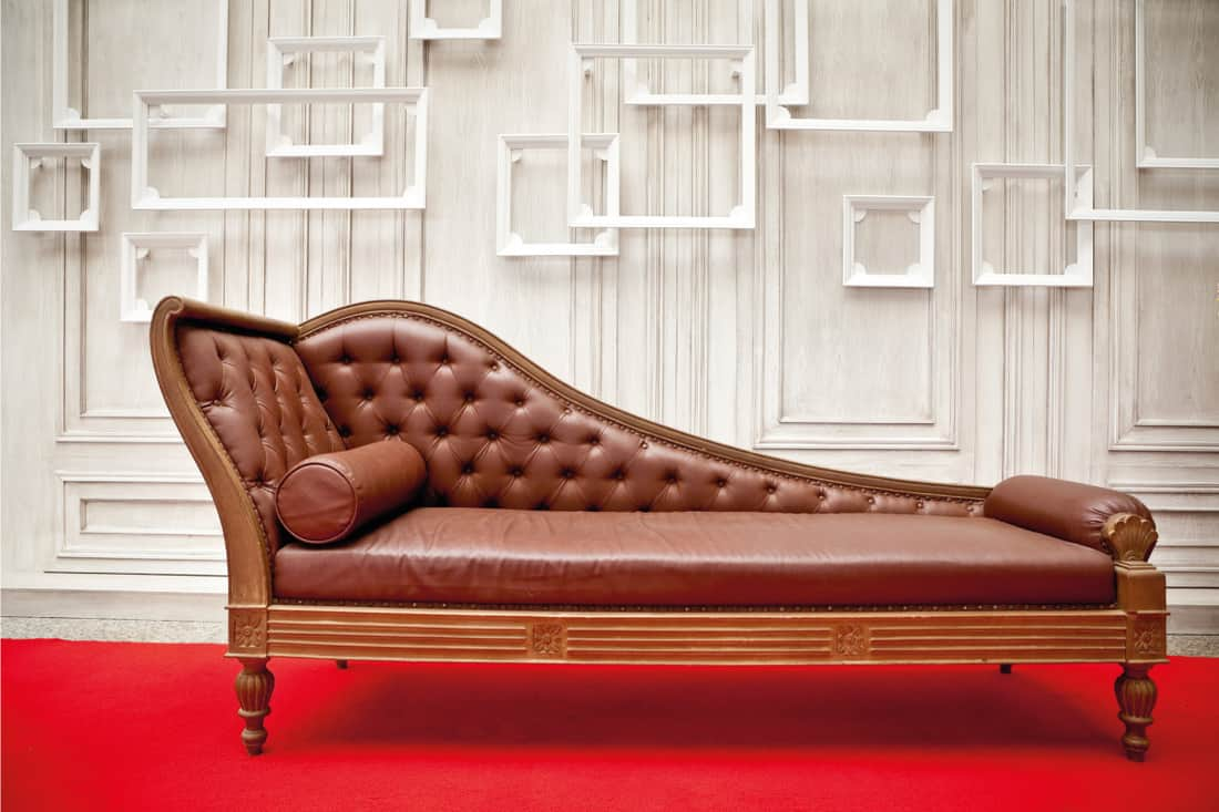 Brown sofa in a white walled room with bright red carpet