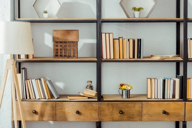 close up of wooden rack with books in living room, How to style a bookcase