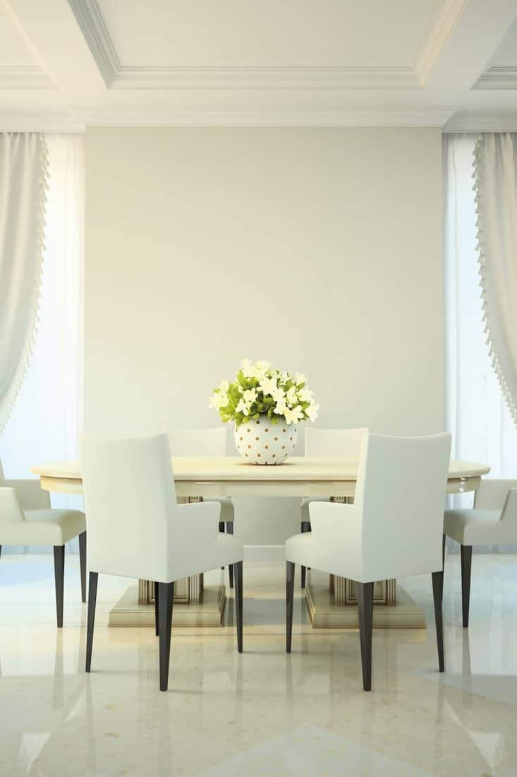 Cream-colored table and chair setup with flower vase in the center of table