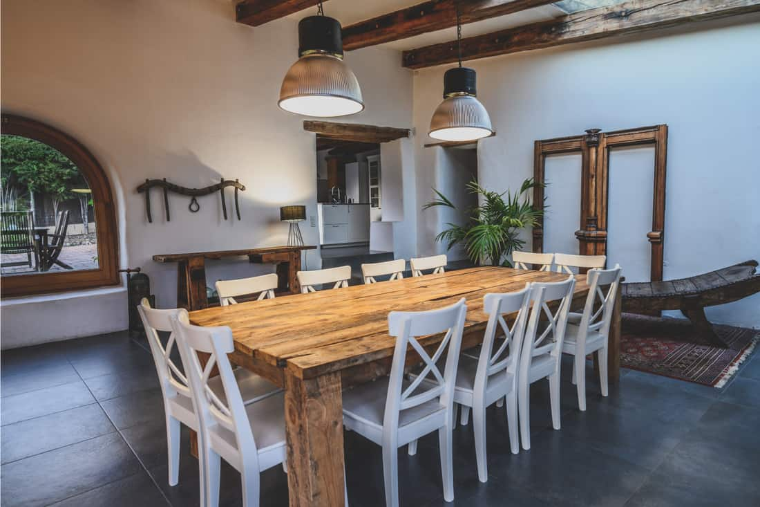 Dining area with large wooden table and chairs in traditional Spanish farmhouse featuring arched window, beamed ceiling and slate flooring